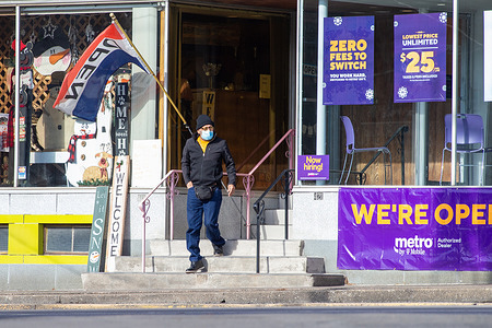A man wearing a face mask exits a T-Mobile store on Sunbury Street in Shamokin.
