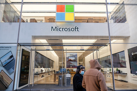 People wearing face masks walk by a Microsoft 5th Avenue retail store in New York City. Microsoft said that the suspected Russian hackers behind a massive US government security breach also viewed some of the company's source code.