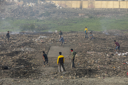 People playing cricket on a dusty field in Dhaka, Bangladesh.
