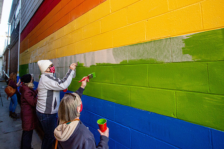 Community members repaint a mural which was defaced with white nationalist graffiti. Dozens of community members gathered at Jake's Cards and Games to repaint the defaced pride mural on the side of the business. Volunteers took turns painting over the spray painted messages from the white nationalist group Patriot Front.