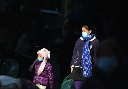 Mother and child wearing face masks as a preventive measure against the spread of coronavirus walk on the street. The Chinese government announced that the covid-19 vaccine is free for all people and the whole cost will be borne by the government.