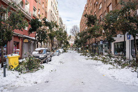 """A street with fallen trees and snow ice during the aftermath. The Filomena snow storm left unprecedented scenarios in Spain due to heavy snowfall. In Madrid the snow left catastrophic scenes. Due to the Mediterranean climate that predominates in the Spanish capital, it had not detected a snow storm like it in half a century. Neighborhood groups, emergency services and municipal services work tirelessly to clean the streets. With the drop in temperature, the snow is expected to turn to ice and continue to cause problems. The Mayor of Madrid, Jose Luis Martinez-Almeida said that """"normal mobility will not be seen until the end of next week"""" and the situation is """"very serious."""""""
