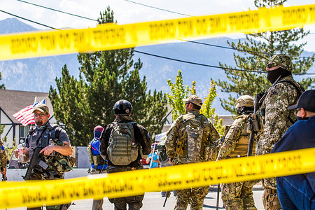 Militia members stand behind the police tape during the demonstration. Militia members rally against a BLM (Black Lives Matter) protest. Hundreds of Militia members easily outnumbered the handful of BLM supporters.