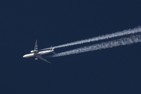 An Emirates Boeing 777 wide body aircraft is seen flying at 40.000 feet in the blue sky over the Netherlands.  The overflying airplane creates contrails, the white condensation vapour lines. The plane is flying from Dubai DXB UAE to England, UK.