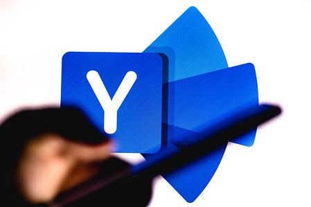 In this photo illustration the Yammer  logo seen in the background of a silhouette hand holding a mobile phone.