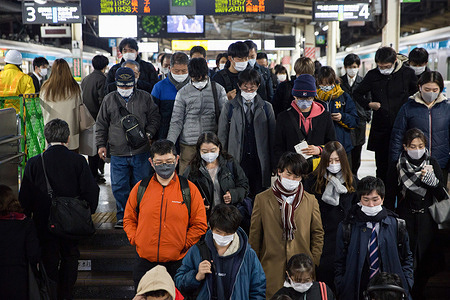 Passengers wearing facemasks at Yokohama Station descend stairs from the platform to enter the main Hall of the station.