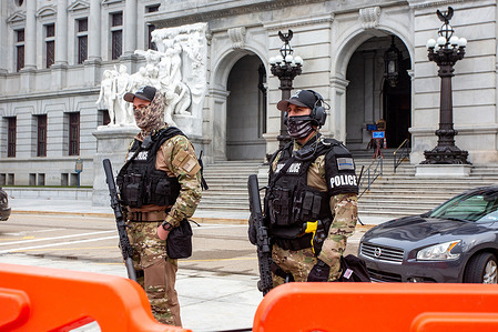 Capitol Police stand guard behind orange barricades at the Pennsylvania Capitol. An FBI bulletin warned that armed protests were planned at all the 50 state capitols in the days leading up to President-elect Joe Biden's inauguration.