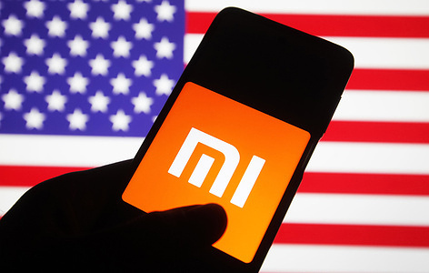 In this photo illustration, Xiaomi logo is seen on a Xiaomi mobile phone screen in front of the flag of the US. The administration of US President Donald Trump added Chinese companies including Chinese electronics company Xiaomi to a blacklist, which will be subject to a new US investment ban, reportedly by media.