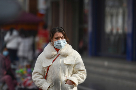 A woman wearing a face mask as a preventive measure against the spread of coronavirus walks on the street.