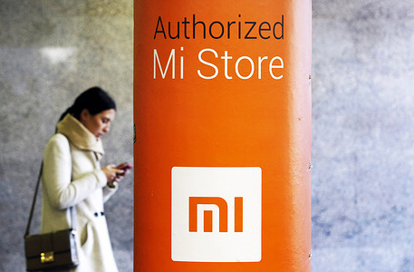 A woman uses her mobile phone as she walks past Xiaomi autorized store.