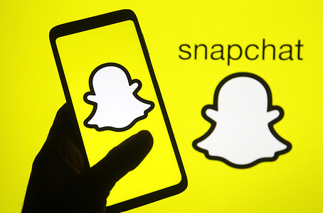 In this photo illustration, Snapchat logo is seen on a mobile phone screen, silhouette of a hand holding a phone with the Snapchat logo in the background.