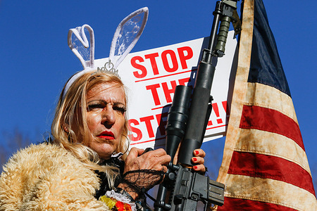 A protestor by the name of Cowboy Barbie, with an AR-15 rifle. Trump supporters gather at the state capital to protest before Biden's inauguration. Crowd size remained small.