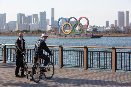 People ride bicycles at Odaiba Marine Park with the Olympic Rings installation in the background.