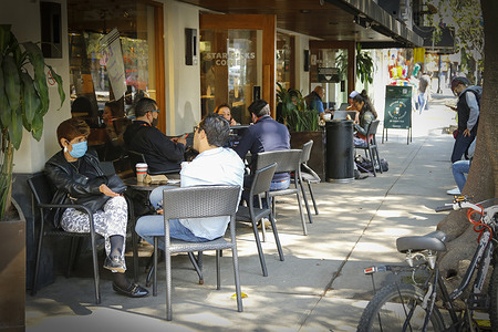 """People dining outdoors at a Starbucks Coffeehouse in Mexico City. Mayor of Mexico City, Claudia Sheinbaum Pardo presented the plan """"Reactivate without risk"""" that allows food businesses and gyms to operate only outdoors after the restaurant industry rebelled against the confinement measures despite the critical situation due to the hospital saturation in the city due to Covid-19 pandemic."""