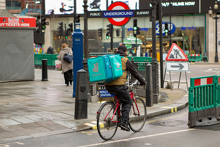 A Deliveroo courier rides along Piccadilly Circus delivering Takeaway food in central London during COVID-19 Lockdown.