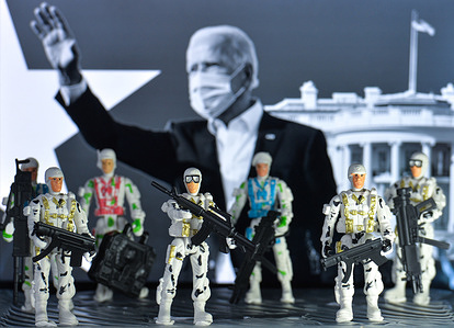 In this photo illustration toy soldiers seen in front of the presidential inauguration advertisement with the image of the US President-Elect, Joe Biden, displayed on a screen in the background.
