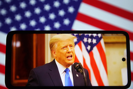In this photo illustration the US President Donald Trump speaks at his farewell address during his last day in office, on a fragment of youtube video displayed on a mobile phone with the US flag in the background.