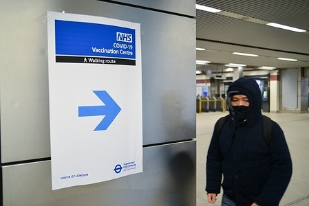 A man passing by a sign, with directions to recently opened NHS Vaccination Centre at Wembley. The site is located near Wembley Stadium, in the Olympic Office Centre. It is one of 25 new sites opening in London this week.