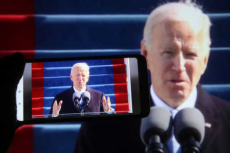In this photo illustration Joe Biden is seen speaking during his inauguration as the 46th president of the United States in Washington, DC on a video translation in facebook displayed on a smartphone and a pc screens.