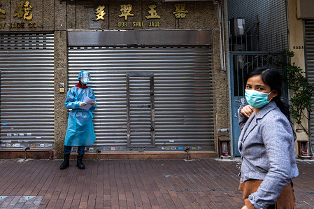 A woman wearing a facemask as protective measure against the COvid-19 coronavirus walks in front of a health worker dressed in PPE (Personal protective equipment) at a mobile Covid-19 testing site. Multiple mobile testing vans are in operation in Hong Kong to provide residents free of charge Covid-19 testing services as the Covid-19 coronavirus continues to spread in the city.