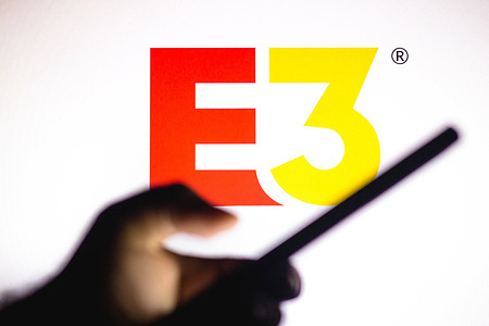In this photo illustration, a hand of a person holds a smartphone with an Electronic Entertainment Expo (E3) logo displayed in the background.