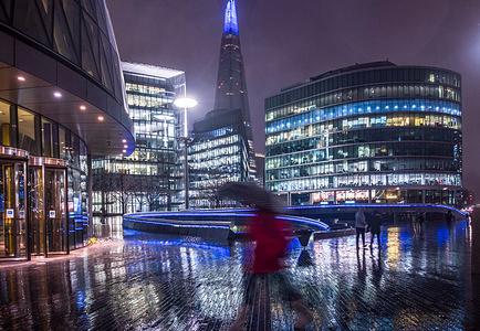 A motion blur image showing  a person walking past The Scoop at More London riverside in London. Met Office forecasts the only sunny day in London in the next 7 days should be on Friday January 22.