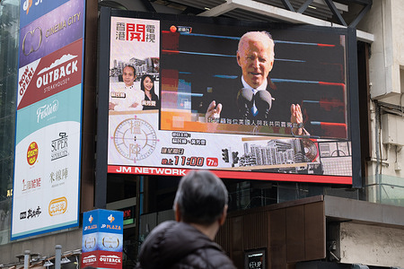A man is seen watching the news report of the inauguration of U.S. President Joe Biden on a large screen.