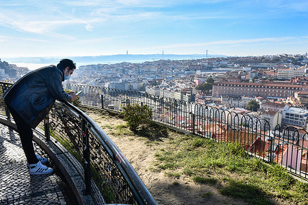 A man wearing a face mask observes the city of Lisbon from the Nossa Senhora de Monte viewpoint.  Portugal has began to implement new lockdown measures in response to the second wave of COVID-19 infections. The government could also suspend schools if a new strain of the virus is detected.