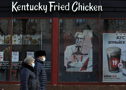 People wearing face masks as a precaution against the spread of Coronavirus walk past a closed KFC fast food restaurant.  In Ukraine over the past day 5583 new cases of the coronavirus disease COVID-19 were recorded.