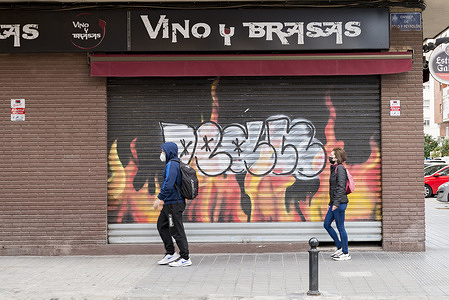 People wearing masks walk past a closed Vino y Brasas restaurant. After the last measures, the infections by Covid19 did not decrease. The Valencia government decreed a total closure of bars and restaurants except for take away food.