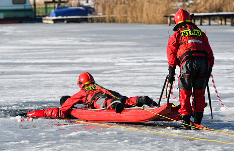 Fire brigade rescuers seen on a rescue board during a training exercise on a frozen lake. The fire brigade from Krakow practiced ice rescue techniques for the retrieval of somebody who has fallen through the ice.