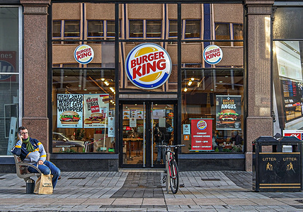 A customer sits outside Burger King fast food store.