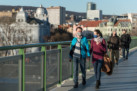 A young couple wearing face masks as a preventive measure against the spread of coronavirus walks along the Old Bridge in Bratislava.  The lockdown declared by the government will last until 7th of February.