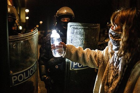 A protester offers policemen a bottle of water as they stand in line during the demonstration. Protest against evictions of artists and social activists from a former Rog bicycle factory which has been used as a squatted alternative social and cultural center for over a decade. The eviction that took place earlier this week included demolition of a social center for the marginalised and socially endangered, as well as a resource and integration center for migrants.