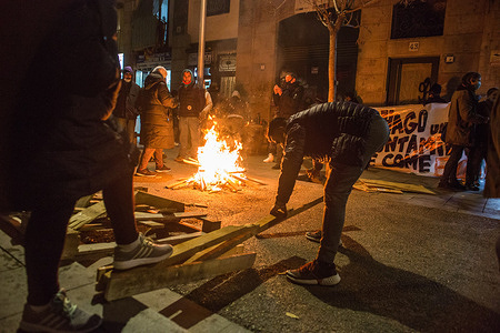 Protesters breaking up wood to keep the bonfire burning during the demonstration. The Housing Union of the Raval neighbourhood of Barcelona has called a demonstration to demand for solutions from the city council on buildings with residents who suffer with power and water cuts.