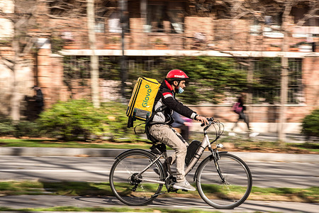 Glovo app delivery man seen riding a bike. The Ministry of Labor of Spain is developing a legislative framework that encompasses the activity of home delivery people known as riders, who operate for digital platforms such as Glovo, Deliveroo, Just Eat or Uber Eats. The new Rider Law would oblige companies to hire their workers and thus end the figure of the false self-employed.