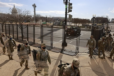 National Guard troops march near the United States Capitol building after the inauguration of President Joe Biden and Vice President Kamala Harris.  The Capitol was breached during an insurrection January 6 just days before the inauguration.