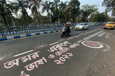 People ride past the road graffiti made at Rabindra sadan area on the occasion of International Mother Language Day. Road graffitis are made on the occasion of International mother language day in Kolkata.