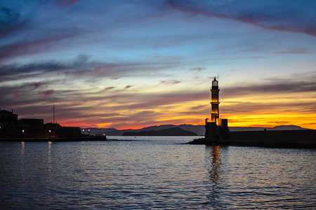 A general view of the port of Chania during the sun set. For over 5 centuries the lighthouse of the old port of Chania stands while it has become a recognition mark of the city all over the world.