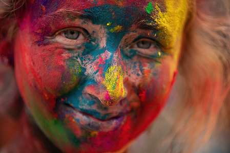 A woman's face covered with Vermilion powder seen during the festival.Holi festival also known as the Festival of Colours, is celebrated for the victory of good over evil and the coming of spring.