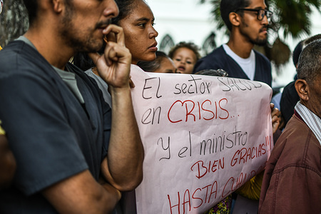 Protesters seen holding placards outside the hospital during a protest. Doctors and staff working at the Vargas Hospital in the city of Caracas, Venezuela, protested demanding improvements in salaries and solutions to the crisis affecting the health system due to the lack of supplies. Workers allowed the press to enter the hospital, controlled by the state, to show how their facilities were. Within minutes, armed groups sent by the national government arrived at the hospital and forcibly removed the media.