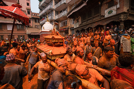 Devotees covered in vermilion powder carry a chariot as they circle the Balkumari Temple during the Sindoor Jatra vermillion powder festival.Revelers carried chariots of the Hindu gods and goddesses and hurled vermillion powder onto each other as part of the celebrations commencing Nepalese New Year.