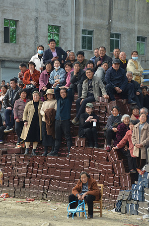 In Gaoyan Village farmers are seen watching a  theatrical performance. On the third day of the third month of the lunar calendar, It is the Shangsi festival of the Chinese nation. Folklore performances and local theater performances will be held in many places, attracting many people to watch.