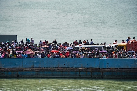 Migrant people get onto an overcrowded ferry to travel home to celebrate Eid al-Fitr amid concerns over the coronavirus disease (COVID-19) outbreak in Munshiganj on the outskirts of Dhaka  Despite the suspension on daytime ferries and the deployment of BGB (Border Guards Bangladesh) troops, the crowds of people hoping to make their way home for Eid are still swelling at Shimulia, a river port.