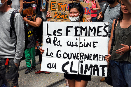 A protester holds a placard during the demonstration.Thousands of people march in France demanding real action on climate change before the law was considered in the Senate.