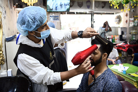A salon staff wearing personal protective equipment (PPE) as a preventive measure against the spread of COVID19 works on a client in salon.