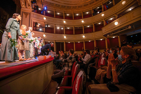 """People wearing face masks as a precaution against the spread of covid-19 applaud actors after the play 'Cat on a Hot Tin Roof'at the Slovene National Theatre. This is the first play after more than six-month of coronavirus closure. As Slovenia reaches the """"Yellow phase"""" the Slovenian government has relaxed some of the COVID measures. Under strict conditions Cultural events are allowed again. Participation of up to 50 persons under condition of RVT (recovered, vaccinated, tested) and seating places with distance can be 50 per cent occupied."""