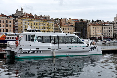 """A view of the histo-boat moored at the Vieux-Port of Marseille, with the basilica of """"Notre-Dame de la Garde"""" in the background. The histo-boat is a 100% electric catamaran used to see the monuments and key places in the history of Marseille from the sea."""