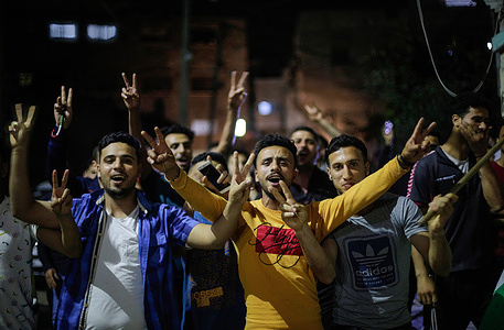Palestinians chant slogans while celebrating on the street after the ceasefire in the northern Gaza Strip.Israel and the two main Palestinian armed groups in Gaza, Hamas and Islamic Jihad, announced a ceasefire on May 21, 2021, with the aim of ending the most devastating conflict between them for a period of seven Years. The truce brokered by Egypt was announced after mounting international pressure to end the 11 days of conflict that claimed the lives of both sides, as Israeli warplanes bombed Gaza with air strikes, while militants fired thousands of rockets towards Israel.