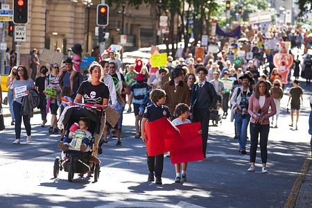 Kids march through the Street while holding placards during the demonstration. Thousands of students and their supporters have walked out of classrooms and workplaces to join School Strike 4 Climate events around the country, becoming part of a global youth-led movement pleading for urgent action on climate change.